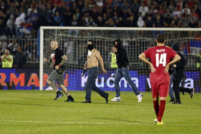 Ivan Bogdanov, left, jailed over a disruption of an Euro 2012 qualifier in Genoa, Italy in 2010, and others invade the pitch during the Euro 2016 Group I qualifying match between Serbia and Albania at the Partizan stadium in Belgrade, Serbia, Tuesday, October 14, 2014. (Photo by Marko Drobnjakovic/AP Photo)