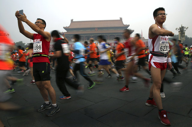 A runner take souvenir photos as others jog past Tiananmen Gate shrouded in haze at the start of 2014 Beijing International Marathon in Beijing, China Sunday, October 19, 2014. (Photo by Andy Wong/AP Photo)