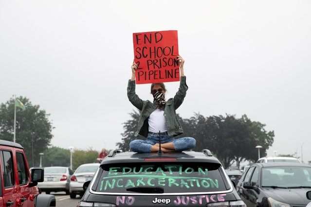 A protester sits on top of a car after a caravan protest in support of a Black Groves High School student, who was jailed due to a probation violation of not keeping up with her online schoolwork, in front of the Oakland County Circuit Court and Prosecutors Office in the Detroit suburb of Pontiac, Michigan, July 16, 2020. (Photo by Emily Elconin/Reuters)
