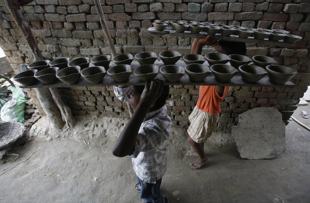 Children of potters carry earthen lamps to dry at a workshop ahead of the Hindu festival of Diwali at Noida in Uttar Pradesh October 18, 2010. (Photo by Parivartan Sharma/Reuters)