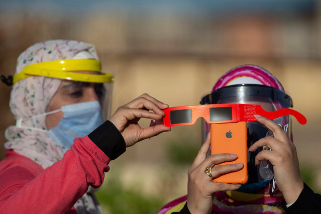 """Women wearing plastic face shields use special protective glasses as a filter to take pictures with an iPhone camera of an annular partial solar eclipse in Cairo, Egypt, 21 June 2020. A partial solar eclipse occurs when a portion of the Earth is engulfed by the shadow (penumbra) cast by the Moon as it passes between our planet and the Sun in imperfect alignment. During this annular eclipse – the first of the decade – the Moon appears to cover the Sun, leaving the Sun's halo as a visible rim forming an annulus, popularly known as the """"ring of fire"""". (Photo by Mohamed Hossam/EPA/EFE)"""