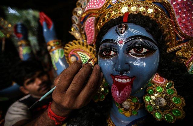 An Indian artist gives finishing touches to the idols of Goddess Kali at a local workshop ahead of Diwali festival, in Mumbai, India, 21 October 2014. Kali, the Goddess of Power, will be worshiped during Diwali festival. Diwali, the festival of lights symbolizing the victory of good over evil which commemorates Lord Ram's return to his kingdom Ayodhya after completing his 14-year exile. This year, Diwali will be celebrated in India on 23 October 2014. (Photo by Divyakant Solanki/EPA)