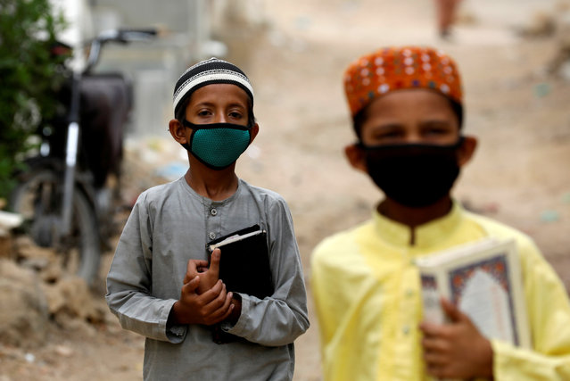 Boys wear protective masks as they head to the madrasa (religious school), during an anti-polio campaign, in a low-income neighborhood as the spread of the coronavirus disease (COVID-19) continues, in Karachi, Pakistan on July 20, 2020. (Photo by Akhtar Soomro/Reuters)