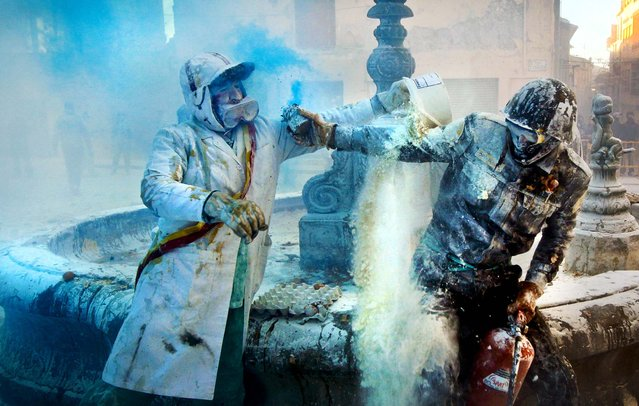 Revelers take part in the festival of Els Enfarinats, in the town of Ibi near Alicante, Spain, December 28, 2012. The celebration, with a battle using flour, eggs and firecrackers has gone on for the past 200 years. (Photo by Alberto Saiz/Associated Press)