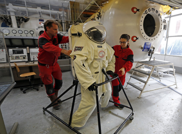 Comex Space division manager Peter Weiss (L) and Comex project engineer Virginie Taillebot (R) move the Gandolfi space suit before a training session in Marseille October 21, 2014. (Photo by Jean-Paul Pelissier/Reuters)