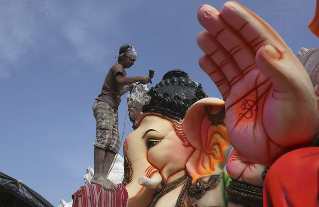 An Indian artist provides final touches to an idol of the elephant headed Hindu god Ganesha before it is carried off for worship to mark Ganesh Chaturthi festival, in Hyderabad, India, Monday, September 5, 2016. The idol will be immersed in water bodies after worship at the end of the festival. (Photo by Mahesh Kumar A./AP Photo)