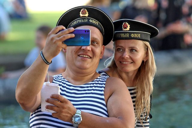 A man and a woman take a selfie on Russian Navy Day in St Petersburg, Russia on July 26, 2020. (Photo by Roman Pimenov/TASS)
