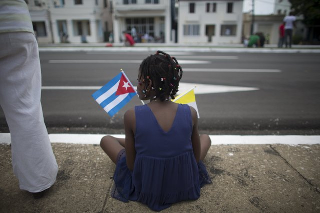 A child holds a Cuban and a Vatican flag as she waits for the arrival of Pope Francis from the airport in Havana, September 19, 2015. (Photo by Alexandre Meneghini/Reuters)