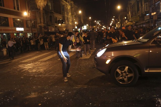 A man blocks traffic as fans celebrate in the street in the Mission District after the San Francisco Giants defeated the Kansas City Royals in Game 7 of the World Series, in San Francisco, California October 29, 2014. (Photo by Robert Galbraith/Reuters)