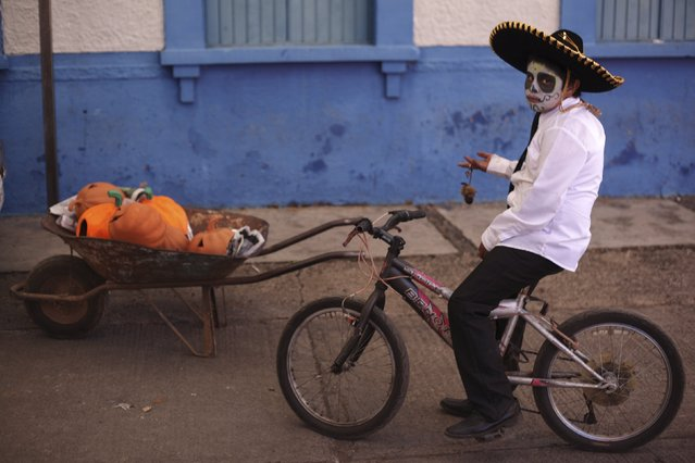 """A boy with his face painted as a skull poses for a photo during the start of the """"Las Catrinas"""" festival,  ahead of the Day of the Dead in Cupula on the outskirts of Morelia , October 26, 2014. La Catrina is a popular figure in Mexico known as """"The Elegant Skull"""". The annual Day of the Dead is observed on November 1 and 2.  REUTERS/Alan Ortega (MEXICO - Tags: RELIGION SOCIETY TRAVEL)"""