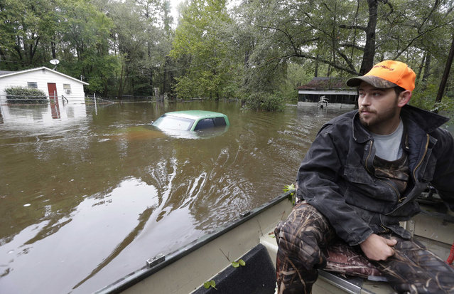 Hunter Baker surveys flood damage to his neighborhood near the flooded Black Creek following heavy rains in Florence, S.C., Monday, October 5, 2015. Flooding continues throughout the state following record rainfall amounts over the last several days. (Photo by Gerry Broome/AP Photo)