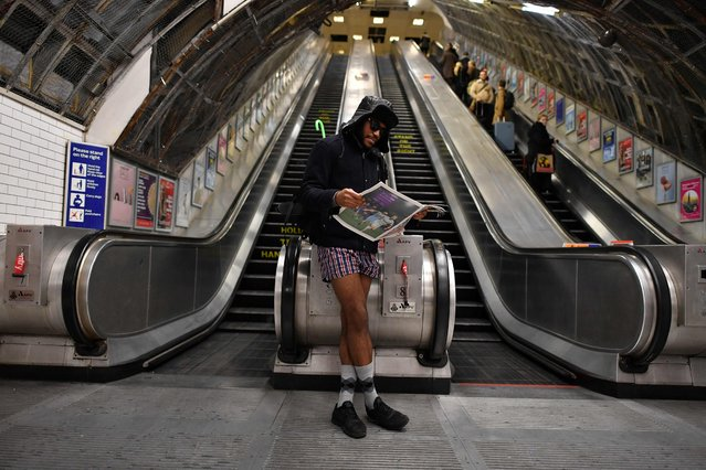 """A man reads a newspaper as he takes part in the annual """"No Trousers On The Tube Day"""" (No Pants Subway Ride) at Liverpool Street Station in London on January 7, 2018. (Photo by Ben Stansall/AFP Photo)"""