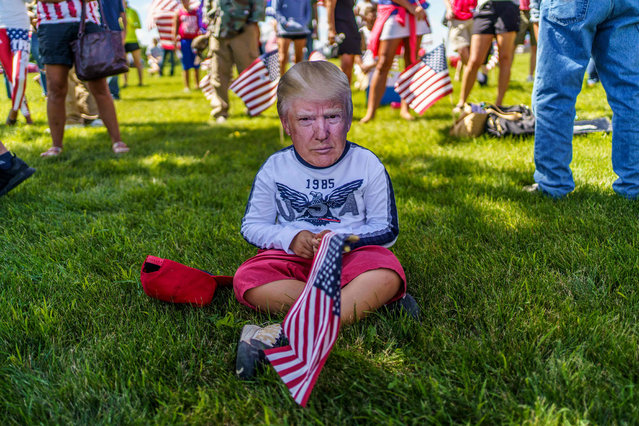 A supporter wears a mask of US President Donald Trump on August 17, 2020 in Mankato, Minnesota as the president delivers remarks on jobs and the economy. (Photo by Kerem Yucel/AFP Photo)