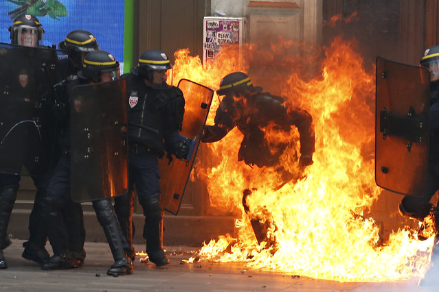 A French riot police officer is surrounded by flames, during a demonstration against the controversial labour reforms of the French government in Paris on September 15, 2016. Opponents of France's controversial labour reforms took to the streets on September 15, 2016 for the 14th time in six months in a last-ditch bid to quash the measures that lost the Socialist government crucial support on the left. Scores of flights in and out of France were cancelled as air traffic controllers went on strike to try to force the government to repeal the changes that became law in July. (Photo by Thomas Samson/AFP Photo)