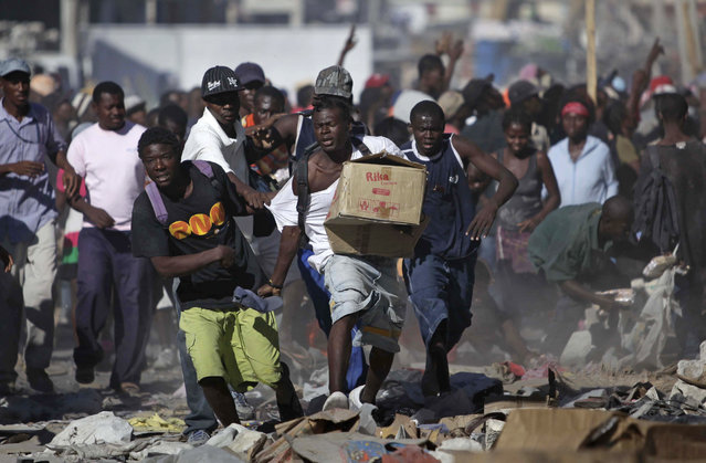 A man runs with a box during sporadic looting in the aftermath of the Jan. 12 earthquake in Port-au-Prince, Thursday, January 28, 2010. (Photo by Ariana Cubillos/AP Photo)