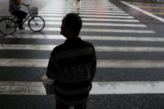 """Wang Cunchun, 90, walks back home from a brokerage house in the rain in Shanghai, China, July 23, 2015. When Wang retired from a stationery store he didn't have much to do. He first invested in stocks in the 1990s. """"Trading stocks is my biggest hobby. I never wanted to make a fortune from stocks. I have 3000 yuan pension every month"""", Wang said. He currently lives with his 60-year-old son in an around 10-square-meter apartment. (Photo by Aly Song/Reuters)"""