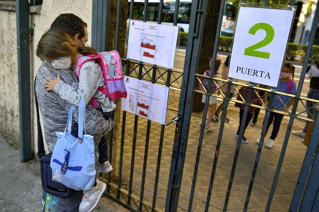 A young student wearing face mask protection to prevent the spread of the coronavirus waits outside to enter in a state school in Pamplona, northern Spain, Friday, September 4, 2020. After six months with all Spanish schools closed by crisis of COVID-19, today is opening a new school year with new rules to prevent the pandemic coronavirus. (Photo by Alvaro Barrientos/AP Photo)