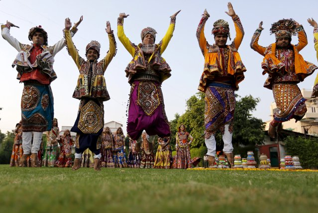 "Performers dressed in traditional attire pose after taking part in rehearsals for the ""garba"" dance ahead of Navratri festival in Ahmedabad, India, October 11, 2015. (Photo by Amit Dave/Reuters)"