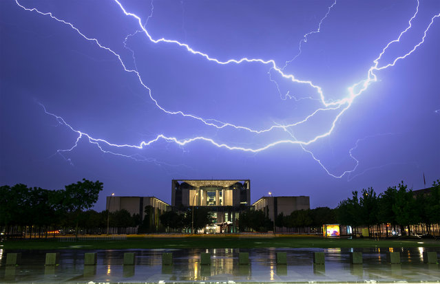 A picture taken with a long exposure made available on 24 May 2016 shows a lightning striking over the German Chancellery in Berlin, Germany, 23 May 2016. (Photo by Paul Zinken/EPA)