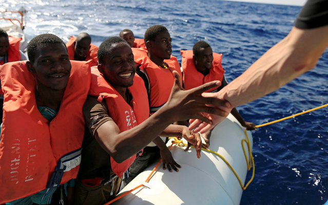 A migrant smiles as he is transferred from a dinghy by members of the German NGO Jugend Rettet during a rescue operation, off the Libyan coast in the Mediterranean Sea September 21, 2016. (Photo by Zohra Bensemra/Reuters)