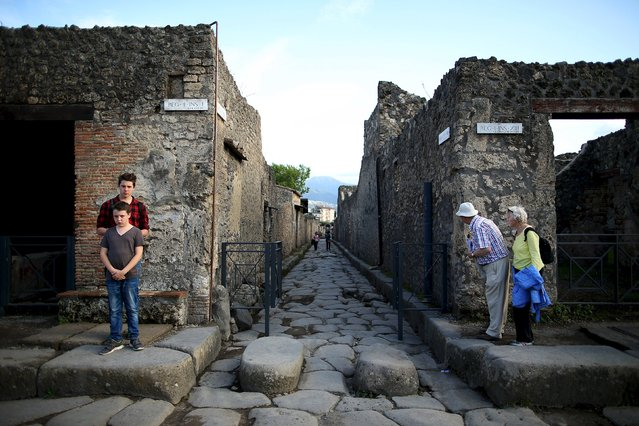 Tourists look down an ancient Roman cobbled street at the UNESCO World Heritage site of Pompeii, October 13, 2015. (Photo by Alessandro Bianchi/Reuters)