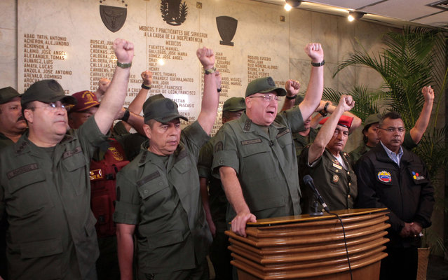 In this photo released by Miraflores Presidential Press Office, Venezuela's Defense Minister Admiral Diego Molero, at the podium, gestures alongside other military leaders during a live televised message to the nation after the vice president announced the death of President Hugo Chavez in Caracas, Venezuela, Tuesday, March 5, 2013.  Molero announced that the military will remain loyal to the constitution in the wake of Chavez's death. (Photo by AP Photo/Miraflores Presidential Press Office)