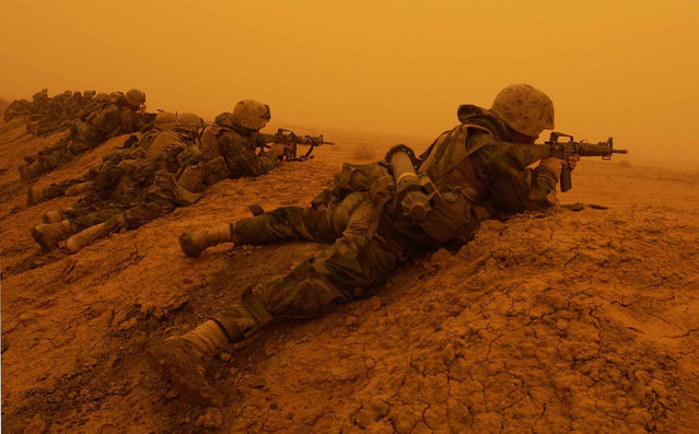 U.S. Marines with 3rd Battalion, 7th Marines, 1st Marine Division, return fire after coming upon a mortar attack during an orange sandstorm on a road south of Baghdad, on March 26, 2003. (Photo by Laura Rauch/AP Photo/The Atlantic)
