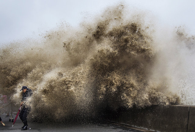 A man dodges tidal waves under the influence of Typhoon Usagi in Hangzhou, Zhejiang province, September 21, 2013. (Photo by Chance Chan/Reuters)