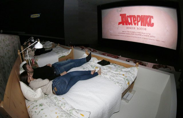 "Spectators await the start of a cinema screening at a Kinostar De Lux Multiplex in the Moscow suburb of Khimki, December 7, 2014. Furniture retailer IKEA has converted one of the cinema halls, completely replacing standard seats with their furniture, according to local media. There are 17 double beds fitted in the hall, which was renamed to ""It wakes love"". (Photo by Sergei Karpukhin/Reuters)"