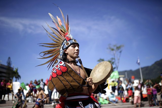 An indigenous dancer participates in a traditional healing ceremony for the mother earth at El Salvador del Mundo Square in San Salvador, December 10, 2014. (Photo by Jose Cabezas/Reuters)