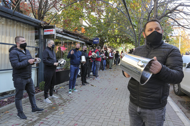 Bar and restaurant owners and employees  pang pots and pans, during a protest opposing the new  measures imposed by the government to control the spread of coronavirus,  in Kosovo's capital Pristina, Saturday, November 7, 2020. Kosovo authorities ordered a weekend lockdown following a spike in daily coronavirus cases. (Photo by Visar Kryeziu/AP Photo)