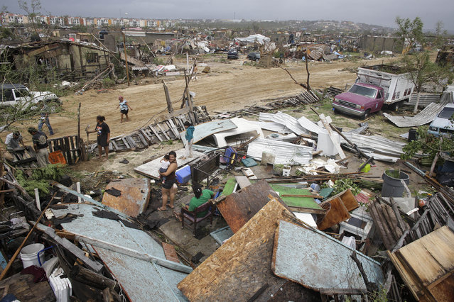 In this September 15, 2014 file photo, people salvage useful remains from homes destroyed by Hurricane Odile in Los Cabos, Mexico. Hundreds of impoverished houses were destroyed in the Unidad Real squatter's settlement and other equally poor neighborhoods. (Photo by Victor R. Caivano/AP Photo)