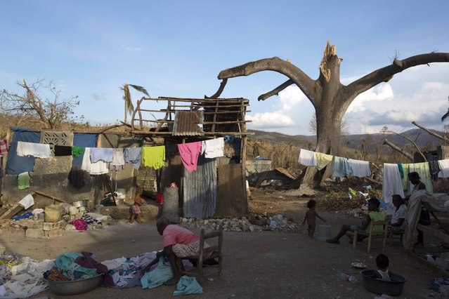 A woman arranges clothes in front of a destroyed house after the Hurricane Matthew in Dame-Marie, Haiti on Monday, October 10, 2016. Jeremie appears to be the epicenter of the country's growing humanitarian crisis in the wake of the storm. (Photo by Dieu Nalio Chery/AP Photo)