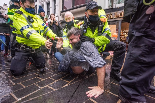 Police officers arrest a protester during an anti-lockdown march in Liverpool, United Kingdom on November 21, 2020. The StandUpX movement organised a protest under the banner March for Freedom, Save Our City. (Photo by Mercury Press)