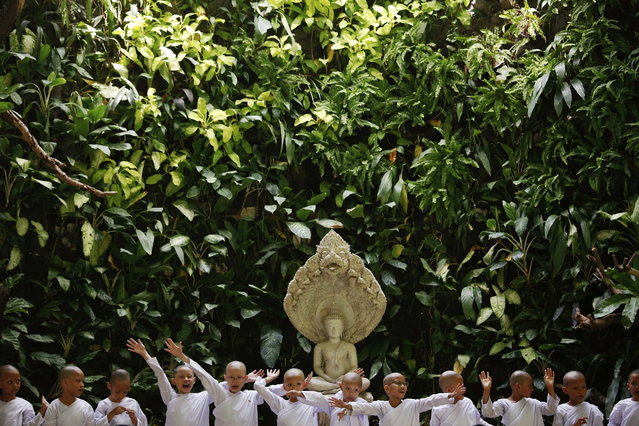 Novice nuns raise their hands during a ceremony at the Sathira-Dhammasathan Buddhist meditation centre in Bangkok April 21, 2013. A group of Thai girls are choosing to spend part of their school holidays as Buddhist nuns, down to having their heads shaven at the meditation centre. The centre, founded in 1987, is a learning community for peace and harmony that has programs open to people regardless of age and gender. (Photo by Damir Sagolj/Reuters)