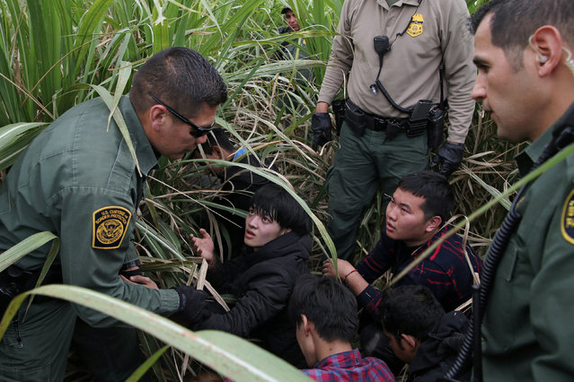 Border patrol agents apprehend immigrants who illegally crossed the border from Mexico into the U.S. in the Rio Grande Valley sector, near McAllen, Texas, U.S., April 3, 2018. (Photo by Loren Elliott/Reuters)