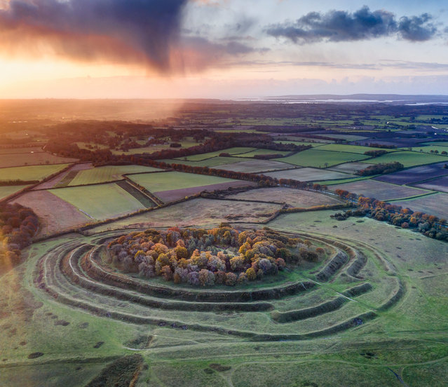 "Shortlisted: Badbury Rings. ""Badbury Rings is one of several large hill forts constructed in the first century BC by the Durotriges tribe. No one knows for sure why these Iron Age traders felt the need to erect such formidable defences; it may have been a response to the political instability resulting from the northward advance of Roman influence through Gaul (France). The Romans' insatiable demand for slaves could well have placed the Britons at risk from raids, and these great ramparts and ditches would have deterred attacks by tribes from the east. Whatever inspired their creation, the concentric rings stand as a dramatic reminder of the wealth and power the Durotriges derived from trade with the Armoricans of Brittany, based around the harbours at nearby Hengitsbury Head. Shot at dawn using a drone, this image reveals the site in the context of its landscape. Visible on the horizon is Poole Harbour, which was a major centre for ceramics in the decades before the Roman invasion of AD43, in the wake of which Badbury was deserted"". (Photo by David Abram/Historic Photographer of the Year 2020)"