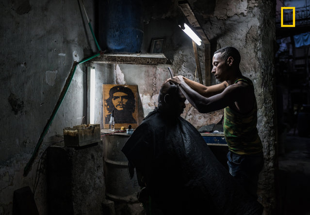 """This Cuban barber has a shop in the run down building he lives in. He has managed to hook up water and electricity and has a steady flow of clients. I couldn't get enough of the atmosphere and visited the shop several times and each time was welcomed in with a smile"". (Photo by Kelly Beckta/National Geographic Travel Photographer of the Year Contest"