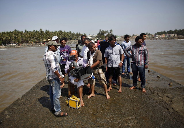 "A cinematographer films, as other members of the crew watch, during the shooting of Bollywood film ""Black Home"" at a beach on the outskirts of Mumbai April 26, 2013. Indian cinema marks 100 years since Dhundiraj Govind Phalke's black-and-white silent film ""Raja Harishchandra"" (King Harishchandra) held audiences spellbound at its first public screening on May 3, 1913, in Mumbai. Indian cinema, with its subset of Bollywood for Hindi-language films, is now a billion-dollar industry that makes more than a thousand films a year in several languages. It is worth 112.4 billion rupees (over $2 billion) and leads the world in terms of films produced and tickets sold. (Photo by Danish Siddiqui/Reuters)"
