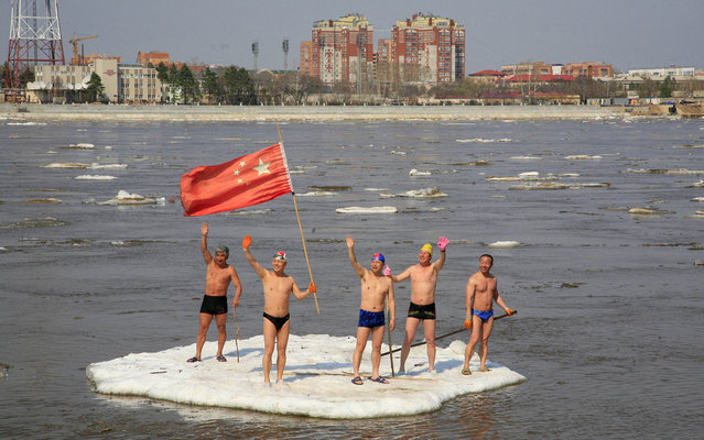 Winter swimmers wave on a piece of drifting ice with a Chinese national flag on the Amur River, in the Chinese border city of Heihe, Heilongjiang province May 6, 2013. (Photo by China Daily/Reuters)
