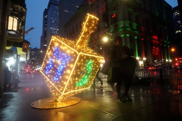 "A dreidel made of Christmas lights called ""Whirl of Whimsy"" sits on the sidewalk along Fifth Avenue during a holiday season installation in the Manhattan borough of New York City, New York, December 4, 2020. (Photo by Carlo Allegri/Reuters)"