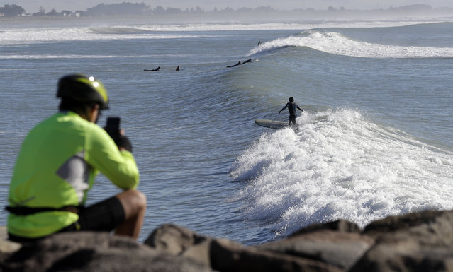 A spectator photographs surfers at Sumner Beach near Christchurch, New Zealand, Tuesday, May 1, 2018. Surfers enjoyed smooth one meter waves at the popular beach on the outskirts of Christchurch. (Photo by Mark Baker/AP Photo)