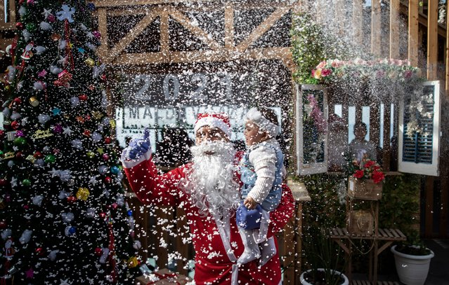 A Palestinian waiter dressed as Santa Clause holds a child for a photograph in a restaurant on the beach in Gaza City, Sunday December 13, 2020. (Photo by Khalil Hamra/AP Photo)