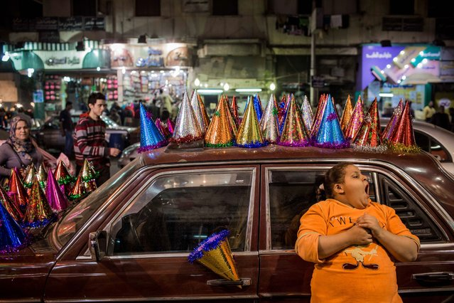 An Egyptian girl yawns as she leans on a car displaying party hats on New Year's Eve in the Shubra district of Cairo, late Wednesday, December 31, 2014. (Photo by Eman Helal/AP Photo)