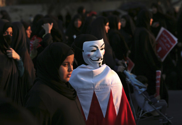 Bahrain: Bahraini pro-democracy protesters, one wearing a Guy Fawkes mask on the back of her head and a national flag, participate in a march near Saar, west of the capital of Manama, Bahrain, Saturday, February 15, 2014. Tens of thousands of protesters marched down a divided four-lane highway, calling for the long-serving prime minister, Sheik Khalifa bin Salman Al Khalifa, to step down and for democracy in the Gulf island kingdom. (Photo by Hasan Jamali/AP Photo)