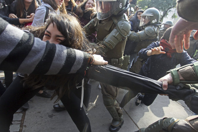 A protester is pulled between fellow demonstrators and police trying to arrest her, during a high school student march for higher quality public education, a few blocks from the presidential palace in Santiago, Chile, Wednesday May 9, 2018. Students protested near the presidential palace instead of the area far from downtown where the government authorized them to gather. (Photo by Luis Hidalgo/AP Photo)
