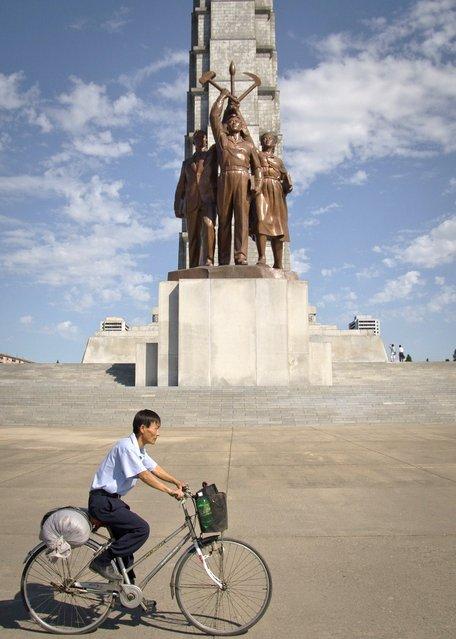 A man cycles past Juche Tower in Pyongyang, September 2011. (Eric Testroete)