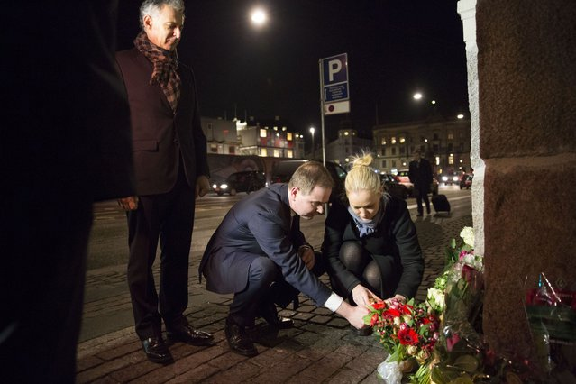 Nicolai Wammen, Danish Minister of Defence, lights a candle in front of the French Embassy in Copenhagen, January 7, 2015, following a shooting by gunmen at the offices of weekly satirical magazine Charlie Hebdo in Paris.  At left is French Ambassador Francois Zimeray. (Photo by Erik Refner/Reuters/Scanpix Denmark)