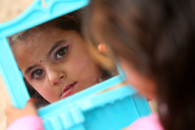 A girl who recently fled the Islamic State's stronghold on the outskirts of Mosul looks into a mirror at Debaga camp, on the outskirts of Erbil, Iraq October 28, 2016. (Photo by Alaa Al-Marjani/Reuters)