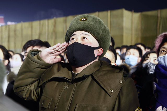 A man salutes during the national flag-hoisting ceremony during celebrations to mark the New Year, at Kim Il Sung Square in Pyongyang, North Korea, early Friday, January 1, 2021. (Photo by Jon Chol Jin/AP Photo)